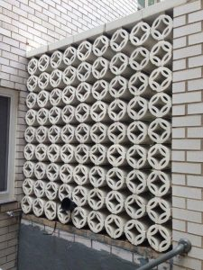 Two sided separation wall--stacked terra cotta pieces meant to draw the eye