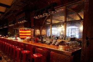 The distressed silvered glass behind the bar casts a glimmering reflection of Cata patrons as they dine in style