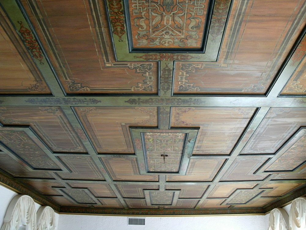 Hand-stenciled ceiling in muted green and red tones